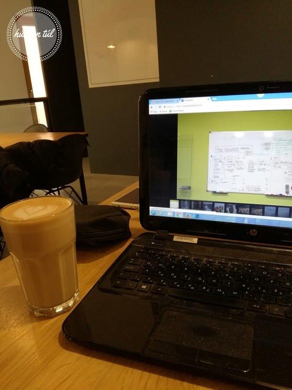 alkotás laptop kijelző előtte nagy pohár kávéval