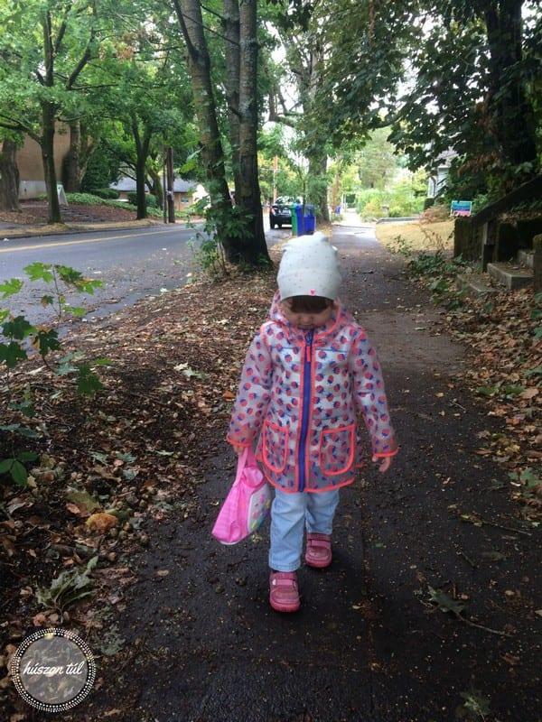 anyamegmondta rózsaszín esőkabátos kislány sétál az utcán